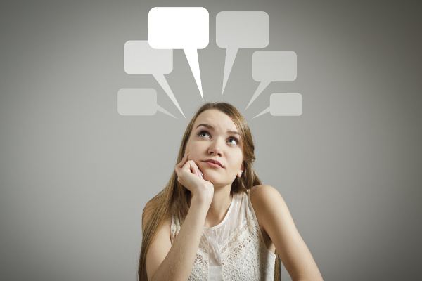Girl in white having an idea with blank speech bubbles over her head.